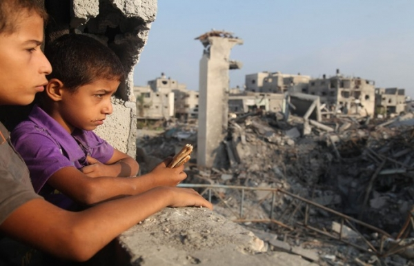 Palestinian children look out of a window of their family home in Gaza
