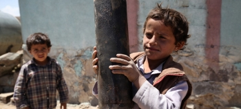 Child holding a piece of exploded artillery shell, landed in a suburb of Sana'a, the capital of Yemen