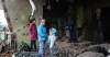 Three children stand in the ruins of a Kurdistan Workers' Party militants' house