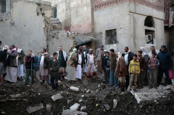 A group of Yemenis staring at some destroyed buildings