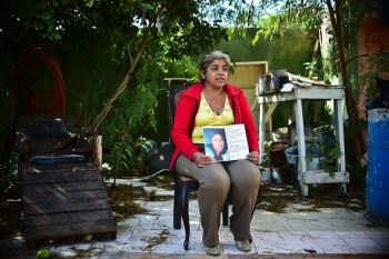 A woman holding a picture of her disappeared daughter