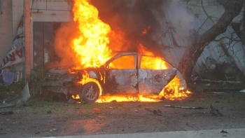 A car burns in the Somali capital after the explosion in the city centre