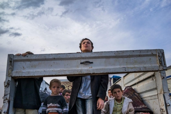 Syrian Kurdish refugees look out from the back of a truck as they enter Turkey from the town of Kobane, Syria.