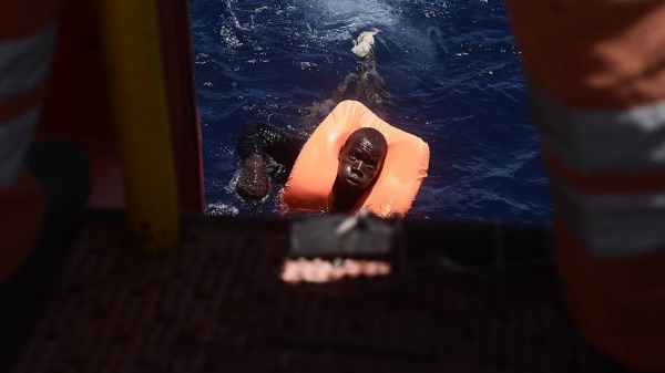 A migrant wearing a lifejacket during a rescue in the Mediterranean Sea