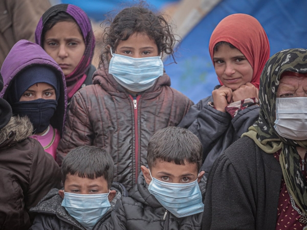 Children and an elderly woman wear facemasks in Idlib, Syria