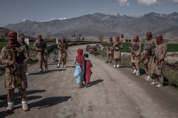 Two boys pass members of a Taliban elite force