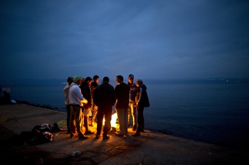 Afghan refugees gather around a fire to warm themselves after arriving on a dinghy from the Turkish coast to the northeastern Greek island of Lesbos