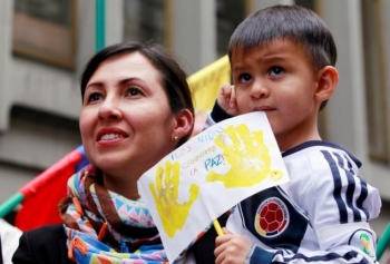 A woman and her son celebrate the signing of a historic ceasefire in Bogota
