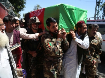 The coffin of Samiullah Rayhan, a religious scholar who was killed while leading prayers at a Mosque in Kabul on 24 May, is carried by Afghan soldiers and supporters.