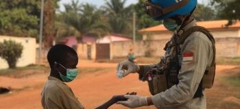 A peacekeeper sanitizing a child's hand