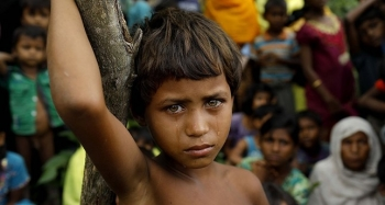 A young Rohingya girl stands in a refugee camp in Bangladesh after fleeing Myanmar