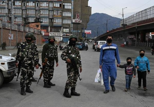 A family walks wearing facemasks in Srinagar, Kashmir