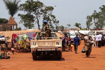 A Blue Helmet UN peacekeeper sits atop a UN vehicle patrolling the town of Bria, while civilians walk around.