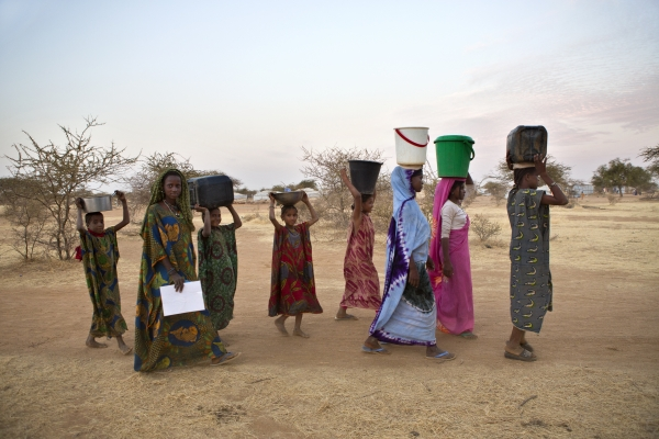 Malian refugee women carry water to their shelters in a nearby camp