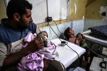 A father and mother hold their sickened children in a makeshift hospital in Eastern Ghouta in Syria last Monday, January 22