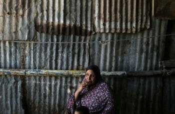 A Palestinian woman sits outside of her house in the Khan Younis refugee camp in southern Gaza.