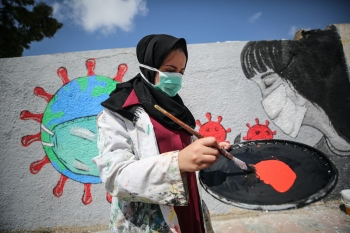 Palestinian artist paints a mural to promote preventive measures against COVID-19, Khan Yunis