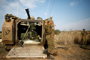 Israeli soldiers with an armoured personnel carrier positioned near the Gaza border in southern Israel.