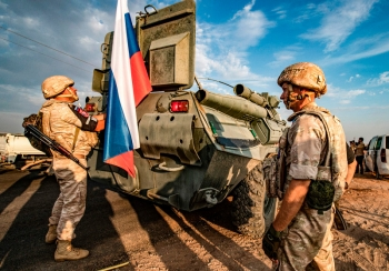 Russian military forces stand near an armored personnel carrier in Syria