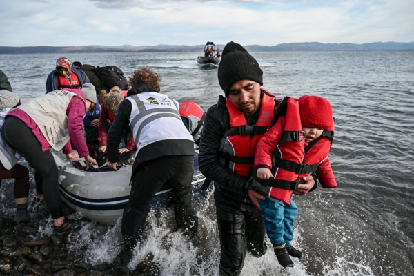 Migrants disembarking a boat after arriving on the Greek island of Lesbos