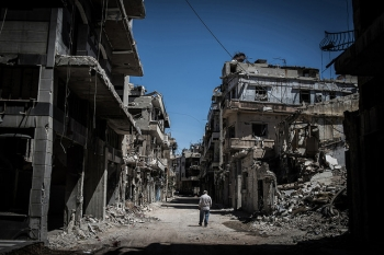 A Syrian Refugee in Homs, Syria walks down a street destroyed by explosive weapons in June 2014.