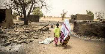 A woman and her child walk through the village Ogossagou after an attack in March 2019 that killed over 150 civilians
