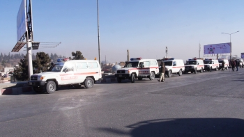 Kabul Ambulance Service vehicles wait to transport victims to the hospital following the hotel attack.