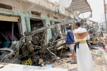 Onlookers view the debris left after a school bus in Yemen was bombed by the Saudi Arabia military who used a US bomb.