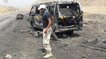 Soldier talks on the phone as he stands at the site of a suicide car bomb attack in Mukalla, Yemen