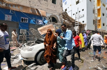 Civilians walk through an attack scene in Mogadishu, Somalia