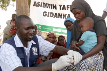 A World Health Organization doctor giving vaccination to a child