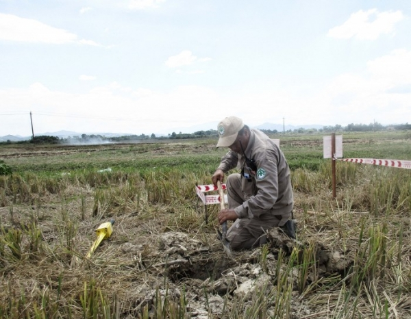 Explosive Ordnance Disposal technician  digging around the marked location to check for cluster munitions