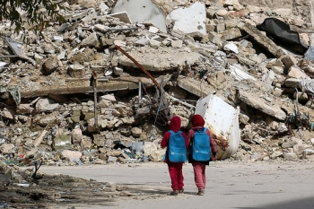 Two  girls in Aleppo walk home from school alongside a mound of rubble