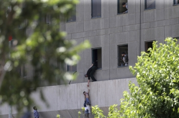 A child is escaping from a window during the assault at the Iranian parliament