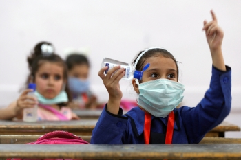 Refugee girl wearing a face mask at school