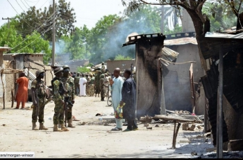Soldiers are shown standing near houses burned by Boko Haram terrorists at Zabarmari, a fishing and farming village near Maiduguri in northeast Nigeria, July 3, 2015.