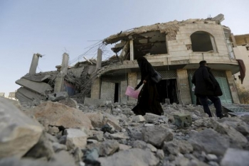 A woman walks past the house of court judge Yahya Rubaid after a Saudi-led air strike destroyed it, killing him, his wife and five other family members on January 25, 2016.