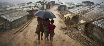 Rohingya refugees from Myanmar stand together during a downpour in Kutupalong refugee settlement, Bangladesh.