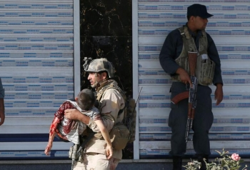 An injured young boy is carried out from the mosque by a member of Afghan special forces
