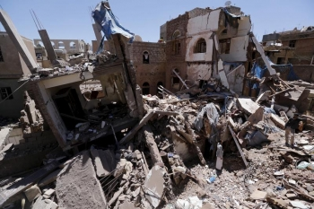 People stand at the site of a recent Saudi-led air strike in Yemen's capital Sanaa, September 11, 2015.