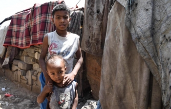 Two brothers stand in a camp for displaced people in Yemen