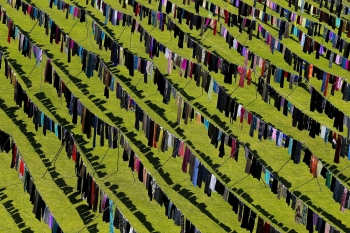 "The art installation ""Thinking of you"" by Kosovan artist Alketa Xhafa- Mripa displays thousands of clothes spread out in the sun inside the stadium of Pristina to show the extension of the use of rape as weapon of war during the conflict in the Former Republic of Yugoslavia."