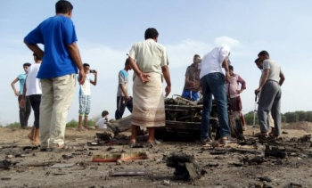 People gather at the site of a car bomb attack in Yemen's southern port city of Aden January 5, 2016.