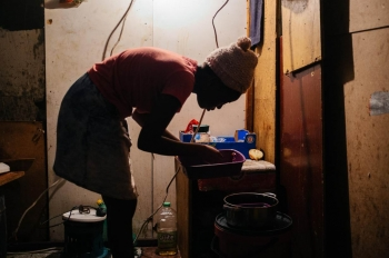 A woman washes dishes and cutlery in inner Johannesburg