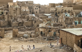 Children play football against a backdrop of destroyed houses in northwest Yemen