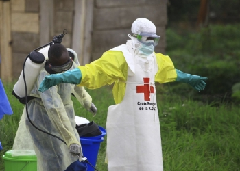 A health worker disinfects a colleague in Beni, North Kivu Province at an Ebola treatment center