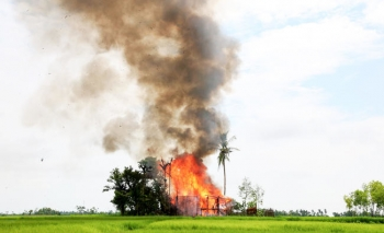 In this 2017 photo, a house burns in Gawdu Tharya village near Maungdaw, Rakhine state