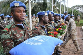 UN Peacekeepers carry a cushion and flowers during the tribute to their fallen fellow soldiers.