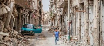Child running through rubble in Benghazi, Libya