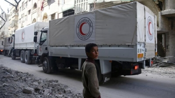 A young boy watching the crossing of IRC trucks delivering humanitarian aid in the city of Douma.
